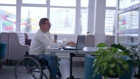 使用巧妙的计算机,网络购物,在轮椅的无效眼镜有信用卡的付付款在互联网 股票视频