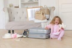 使用带着一个减速火箭的手提箱的愉快的小女孩 免版税图库摄影