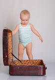使用带着在灰色背景的手提箱的女婴 免版税库存照片