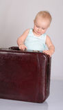 使用带着在灰色背景的手提箱的女婴 库存照片