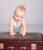 使用带着在灰色背景的手提箱的女婴 库存图片