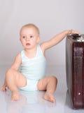 使用带着在灰色背景的手提箱的女婴 免版税库存图片