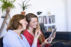 使用平板电脑计算机和微笑时,两美丽的年轻女人在家坐沙发,当 免版税图库摄影