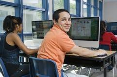 使用平面屏幕显示器的高中学生 免版税库存图片
