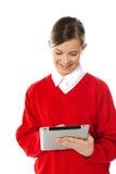 使用年轻人的女孩愉快的个人计算机片剂 库存图片