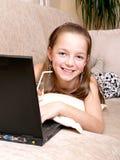 使用年轻人的女孩膝上型计算机 免版税图库摄影
