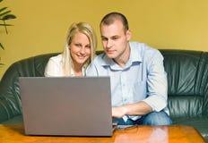 使用年轻人的有吸引力的夫妇膝上型计算机 免版税库存图片