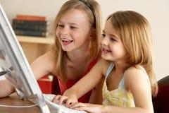 使用年轻人, 2个计算机女孩回家 免版税库存照片