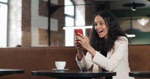使用应用程序的女商人在坐在现代办公室的智能手机 桃红色衣服的美丽的偶然女性专家 免版税库存照片
