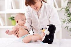使用微笑的医生的儿科医生和享用与小患者 免版税图库摄影