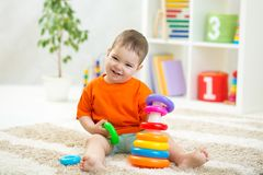 使用户内与发展玩具的小孩男孩坐软的地毯 库存图片