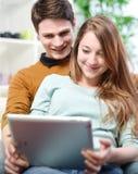 使用户内数字式片剂的年轻夫妇在沙发 图库摄影