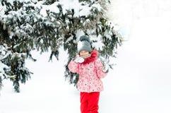 使用户外与雪的一个美丽的小孩女孩的画象 享受一个冬日的愉快的小孩在公园或 免版税库存图片