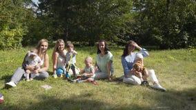 使用户外在夏天公园的小组愉快的孩子 母亲照看他们的孩子坐草 股票录像