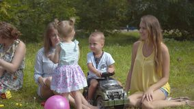 使用户外在夏天公园的小组愉快的孩子 母亲照看他们的孩子坐草 股票视频