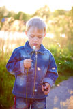 使用户外在夏天在一晴朗的温暖的天,草,绿色,自然的盖帽的小男孩 免版税库存图片