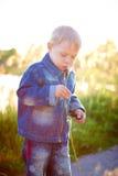 使用户外在夏天在一晴朗的温暖的天,草,绿色,自然的盖帽的小男孩 免版税图库摄影