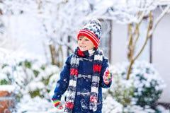 使用户外在强的降雪期间的五颜六色的衣裳的滑稽的小孩男孩 免版税库存图片