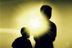 使用户外在日落silhou的母亲和儿子的剪影 库存照片