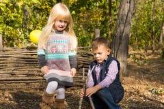 年轻使用户外在森林地的男孩和女孩 免版税库存照片
