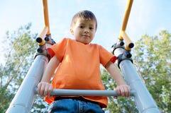 使用户外在酒吧健身房的男孩 在操场,儿童活动的孩子 有儿童的乐趣 活跃健康童年 库存照片