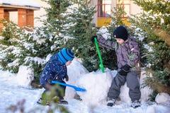 使用户外在降雪期间的五颜六色的衣裳的两个小孩男孩 与孩子的活跃休闲在冬天在冷的天 机会 库存照片