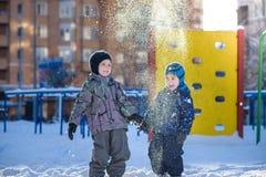 使用户外在降雪期间的五颜六色的衣裳的两个小孩男孩 与孩子的活跃休闲在冬天在冷的天 机会 免版税库存照片