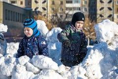 使用户外在降雪期间的五颜六色的衣裳的两个小孩男孩 与孩子的活跃休闲在冬天在冷的天 机会 免版税库存图片
