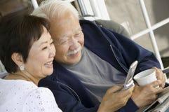 使用户外手机的资深夫妇 免版税库存图片