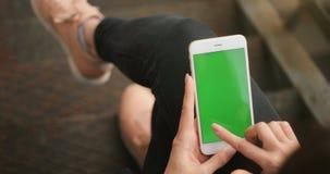 使用户外电话绿色屏幕城市环境红色戏院4K的女孩递把握企业智能手机镀铬物关键 股票录像