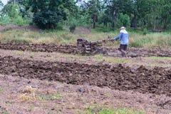 使用手扶拖拉机的泰国农夫为耕种的土壤为准备种植园 图库摄影