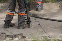 使用手提凿岩机在路修理的男性工作者气动排种式播种机机械 库存图片