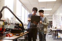使用手提电脑的两位男性大学生在科学机器人学或工程学类 库存照片