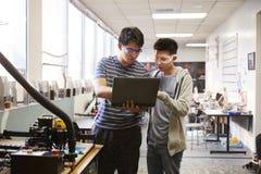 使用手提电脑的两位男性大学生在科学机器人学或工程学类 免版税库存照片