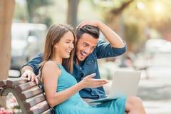 使用手提电脑的愉快的年轻夫妇坐长凳在室外的城市 图库摄影