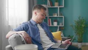 使用手提电脑,年轻人坐沙发在家做视频通话 股票视频