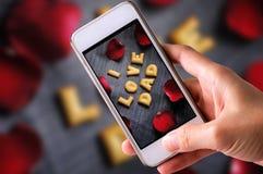 使用手机为曲奇饼ABC照相以词我的形式爱与红色玫瑰花瓣的爸爸字母表在老斜纹布backgroun 图库摄影
