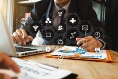 使用手机和便携式计算机的商人在木书桌上 库存图片