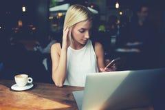 使用手机和便携式计算机的迷人的女学生在休息期间在咖啡店 图库摄影