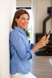 使用手机和家的微笑的老妇人 免版税库存图片