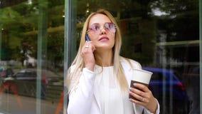使用手机和拿着咖啡杯的年轻美丽的女商人外面 影视素材