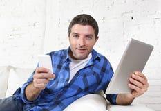 使用手机和数字式片剂垫在长沙发微笑的年轻可爱的30s人愉快 免版税库存照片