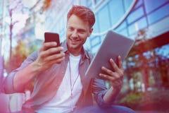 使用手机和数字式片剂的商业主管反对办公楼 库存图片
