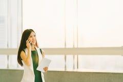 使用手机和数字式片剂的美丽的亚裔妇女在现代办公室、营业通讯或者智能手机技术 库存图片