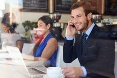 使用手机和膝上型计算机的商人在咖啡店 图库摄影