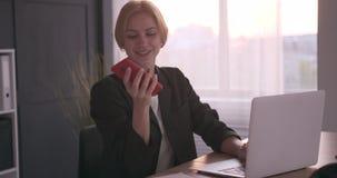 使用手机和膝上型计算机的女实业家在办公室 股票录像