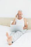 使用手机和膝上型计算机的微笑的成熟人在床 免版税图库摄影