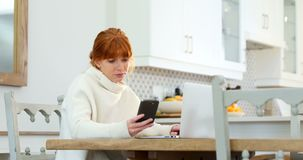 使用手机和膝上型计算机的美丽的妇女,当食用咖啡4k时 影视素材