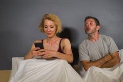 使用手机在床和可疑沮丧的丈夫或男朋友感觉翻倒上怀疑背叛的女朋友或妻子和 免版税库存照片