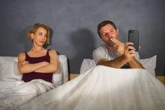 使用手机在床和可疑沮丧的妻子或女朋友感觉翻倒上怀疑背叛的丈夫或男朋友和 库存图片